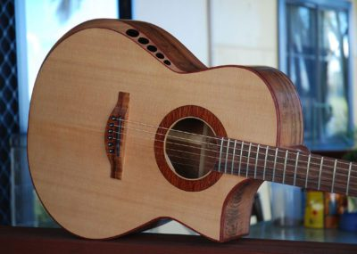 Custom hand made acoustic guitar with cutaway body featuring a fluted arm comfort bevel aiming sound to player's right ear to provide an enhanced playing experience.